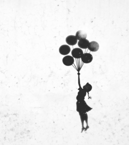 Concrete wall with Banksy painting of girl with balloons floating away